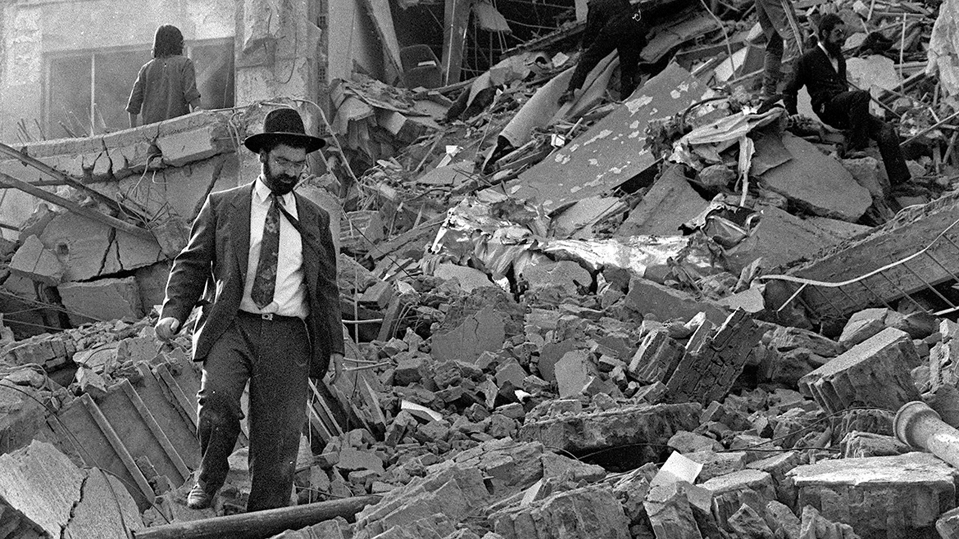 (FILE) A man walks over the rubble left after a bomb exploded at the Argentinian Israeli Mutual Association (AMIA in Spanish) in Buenos Aires, 18 July 1994. Argentinian prosecutors formally charged Iran and the Shiite militia Hezbollah 25 October 2006 in the 1994 bombing of the Argentine Jewish Mutual Associationa in Argentina, which killed 85 people and injured 300. Prosecutors called for the arrest of top Iranian authorities at the time, including then-president Akbar Hashemi Rafsanjani. Next July 18 marks the 20th anniversary of the attack. AFP PHOTO/ALI BURAFI