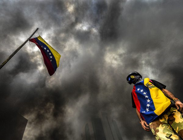 TOPSHOT - An anti-government demonstrator stands next to a national flag during an opposition protest blocking the Francisco Fajardo highway in Caracas on May 27, 2017.  Demonstrations that got underway in late March have claimed the lives of 58 people, as opposition leaders seek to ramp up pressure on Venezuela's leftist president, whose already-low popularity has cratered amid ongoing shortages of food and medicines, among other economic woes. / AFP / LUIS ROBAYO